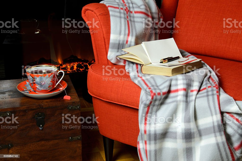 Blanket and tea cup by the fireplace stock photo
