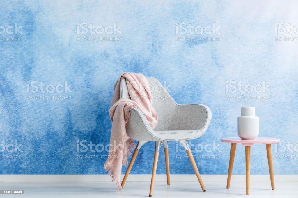 Decke Auf Einen Sessel Und Couchtisch Mit Einer Weißen Vase Set An