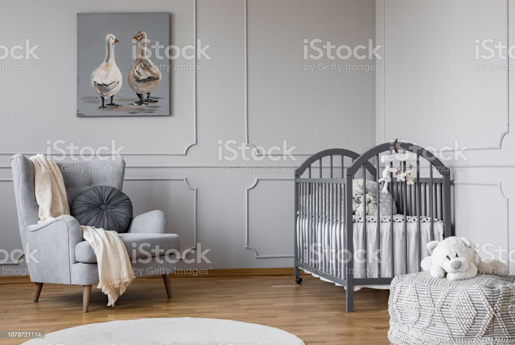 Blanket on armchair near ved in grey child's bedroom interior with poster and toy on pouf. Real photo stock photo