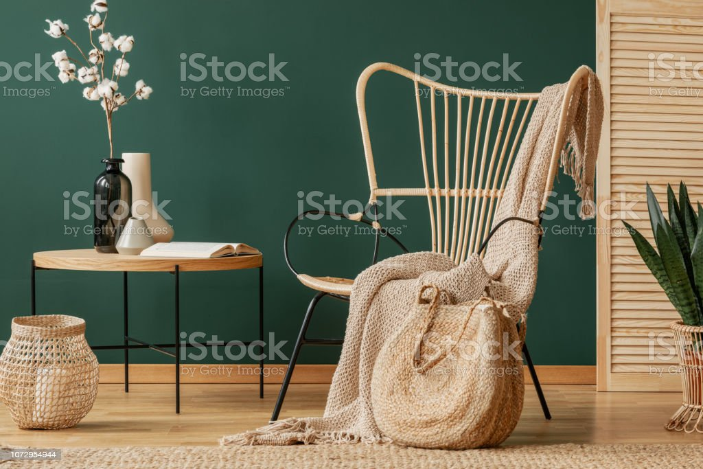 Blanket on rattan armchair next to table with flowers in green flat interior with lantern. Real photo - Foto stock royalty-free di Ambientazione interna