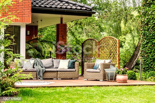 istock Blanket thrown on garden sofa, basket with pillows standing next to armchair on wooden terrace 1007175402