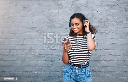 Shot of a young woman using a cellphone while wearing headphones against a grey wall