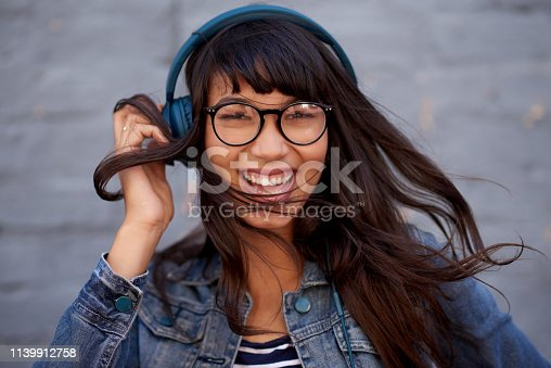 Portrait of a young woman wearing headphones against a grey wall