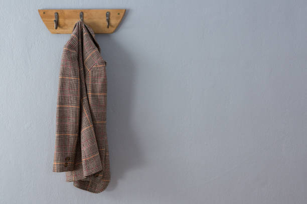 Blazer hanging on hook Blazer hanging on hook against wall blazer jacket stock pictures, royalty-free photos & images