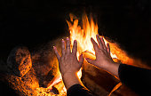 Female hands with fingers splayed over warm fire with orange burning flames. Tranquil scene of evening rest. Selective focus