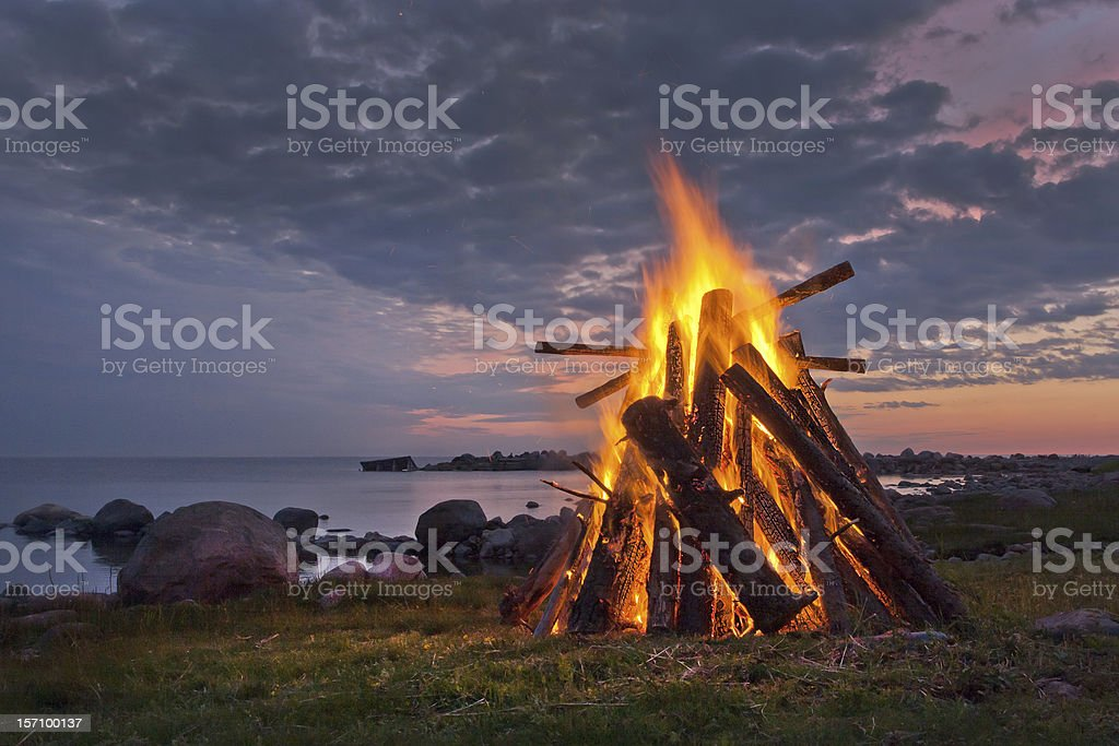 Blazing bonfire near a body of water at dusk stock photo