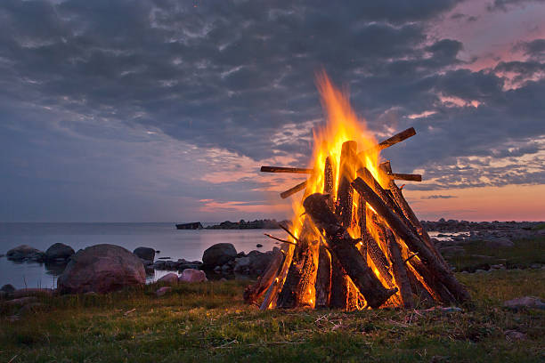 Blazing bonfire near a body of water at dusk Bonfire on the coast in a white Nordic summer night.  bonfire stock pictures, royalty-free photos & images