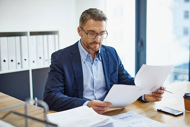 Blazing through his paperwork Shot of a mature businessman reading a document at his desk in an office document stock pictures, royalty-free photos & images