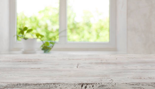 Bleached vintage wooden tabletop with blurred window for product display stock photo