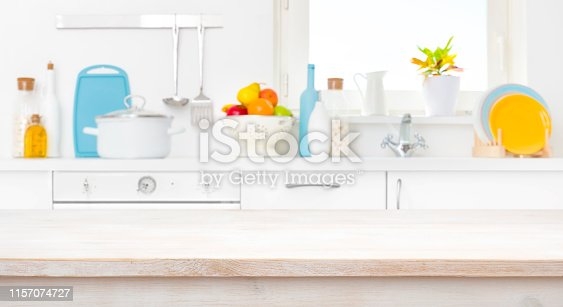 607472174istockphoto Bleached wooden table in front of blurred sunny kitchen window 1157074727