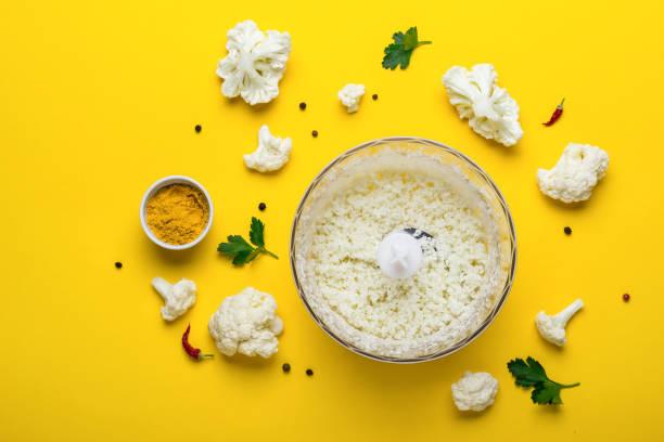 갓된 콜리플라워 쌀과 노란색 배경에 향신료와 함께 믹서 기 그릇 - 십자화과 뉴스 사진 이미지