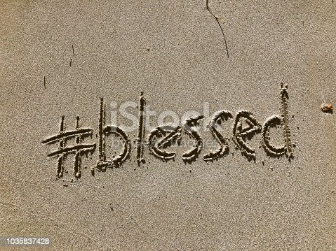 Blessed message with a modern social media hashtag twist written in the sand on the beach