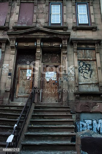 New York City, NY, USA - November 25, 2015: View of a long time derelict boarded up brownstone building in Harlem. Graffiti on wall. 144-146 west 129th street.