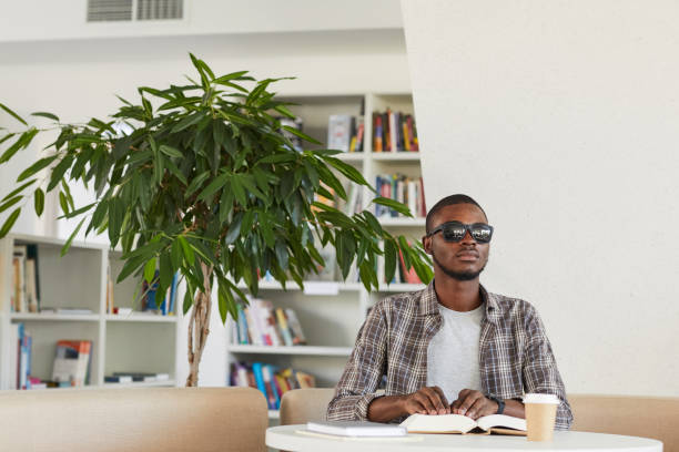 Blind African Man Reading Book in Library stock photo