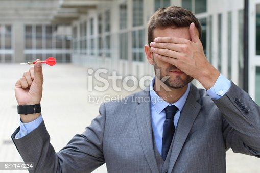 Blind businessman holding a dart.