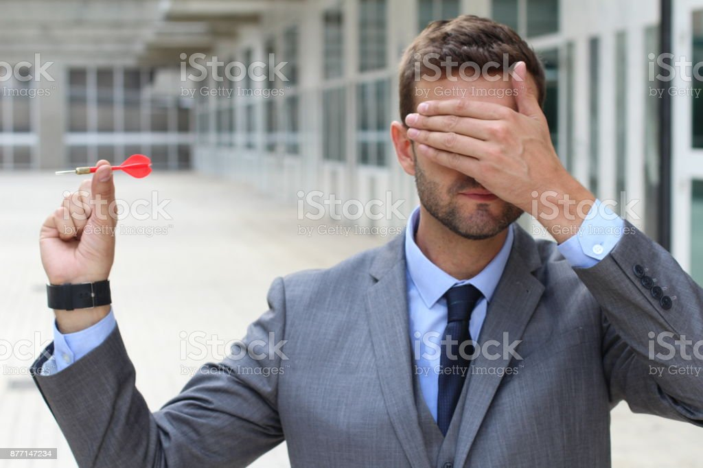 Blind businessman holding a dart stock photo
