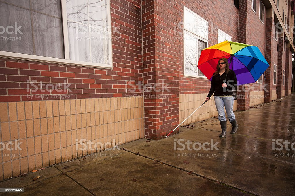 Blind Cane User with Bright Umbrella stock photo