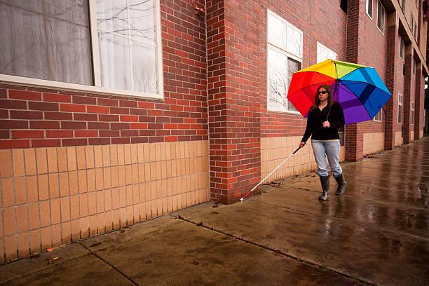 Blind Cane User with Bright Umbrella stock photo