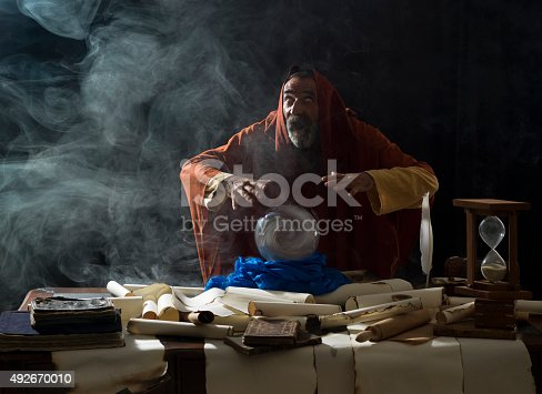 Blind fortune teller magician in fantastical smoky atmosphere using crystal ball.He is wearing a brown frock with hood.The background is black.Smoke is coming out from the desk.There are large amount of scrolls, few antique black books and a hourglass on desk.The eyes of model has turned to white.Shot with a medium format camera Hasselblad.