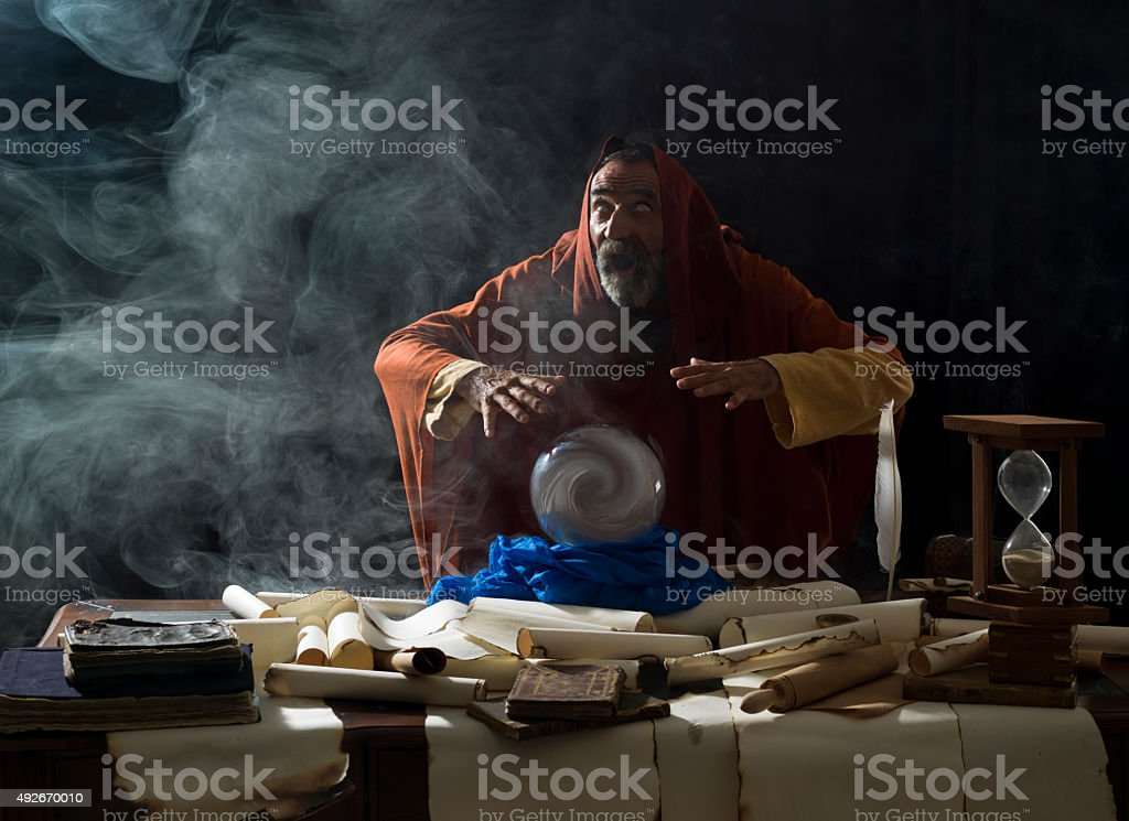 Blind fortune teller in fantastical costume using crystal ball stock photo