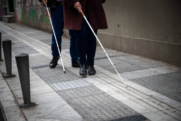 blind man and woman walking on the street using a white walking stick blind man and woman walking on the street using a white walking stick blind eyes stock pictures, royalty-free photos & images