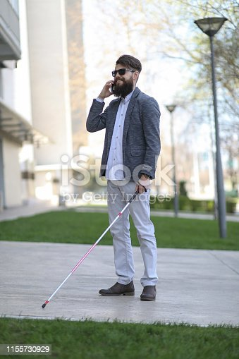 Young beautiful bearded man with white support cane walking down the street and talking over the phone