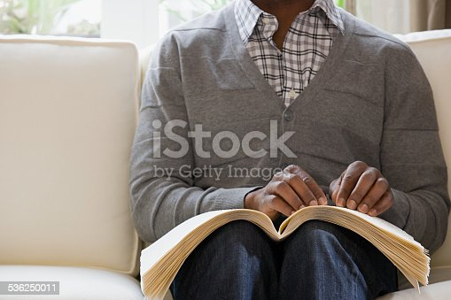 istock Blind man reading a braille book 536250011
