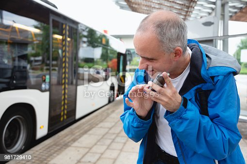 Midadult blind man, wearing casual blue clothing, holding his cellphone near his face, listening to information. He is standing at a bus station