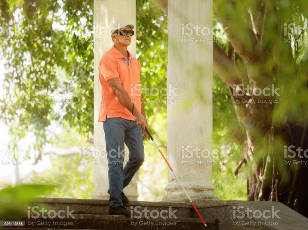 Blind Man Walking And Descending Steps In City Park'n stock photo