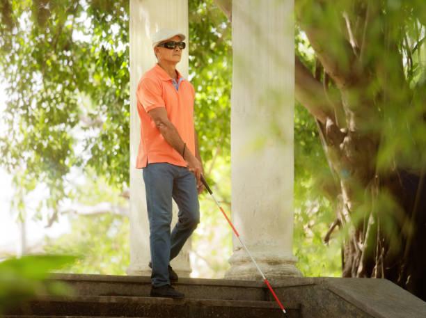 Blind Man Walking And Descending Steps In City Park