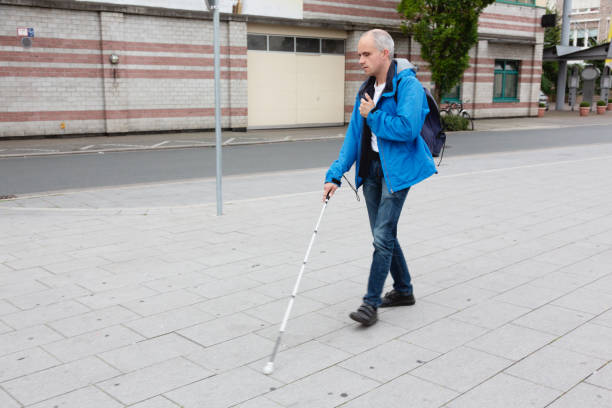 Blind man walking in street supported by cane stock photo