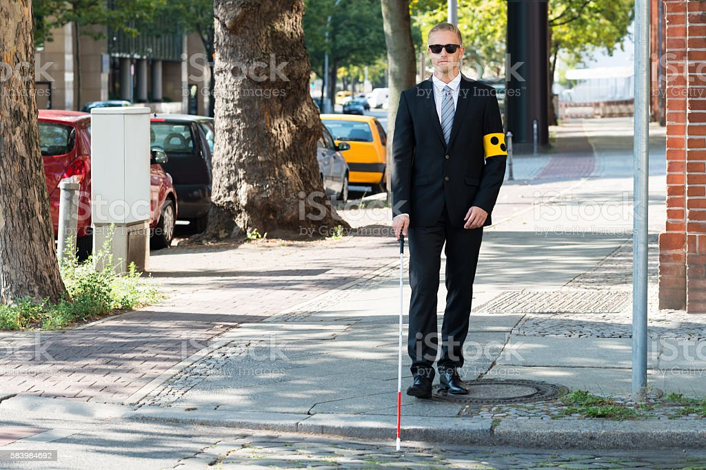 Blind Man Walking On Sidewalk Holding Stick stock photo