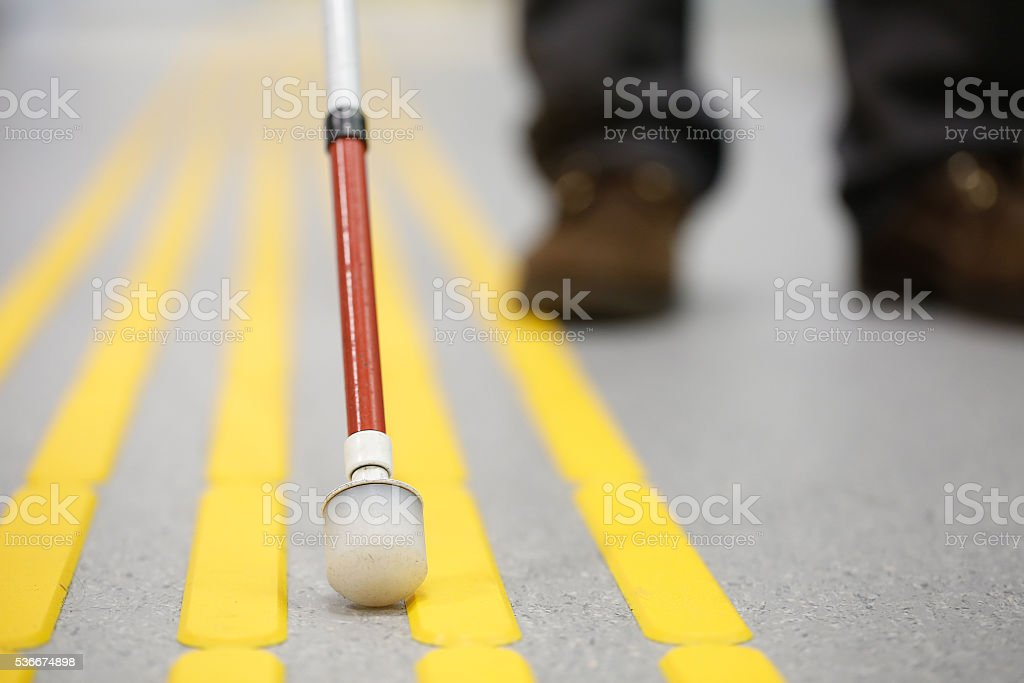Blind pedestrian walking on tactile paving stock photo