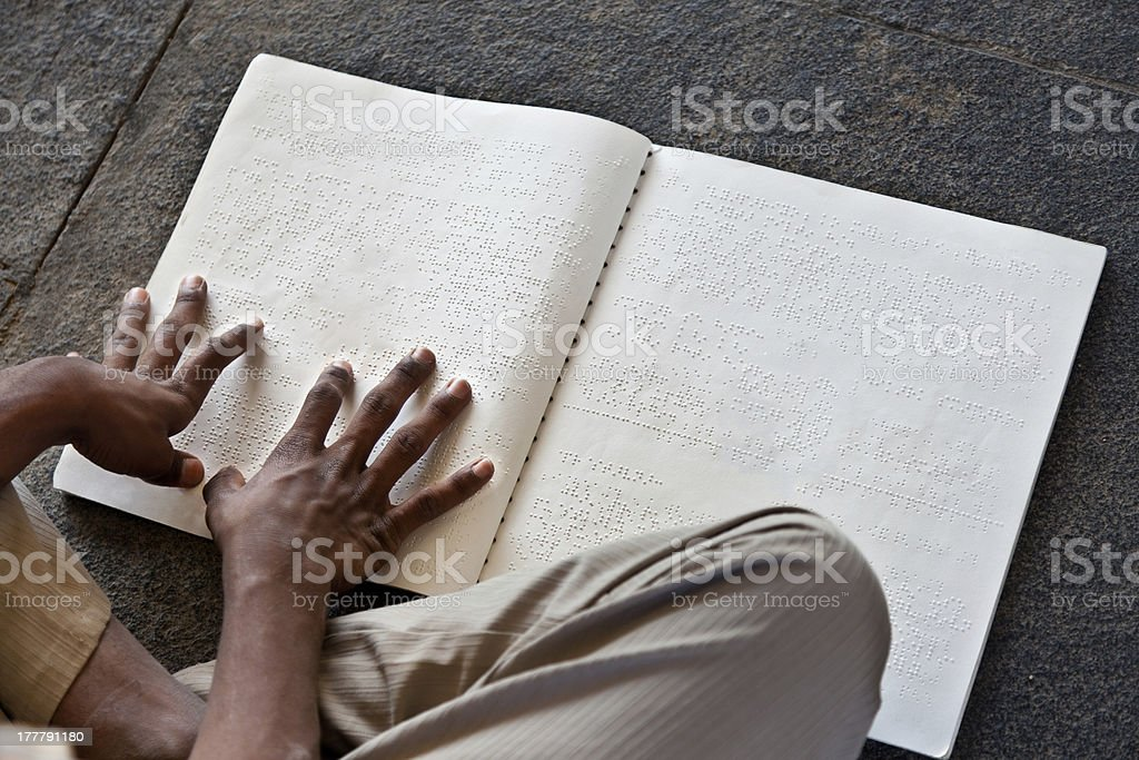 Blind person reads Braille with hands stock photo