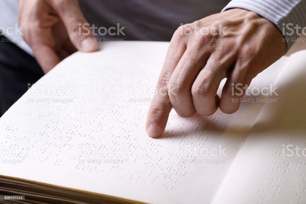Blind person touching book, written in braille writing stock photo