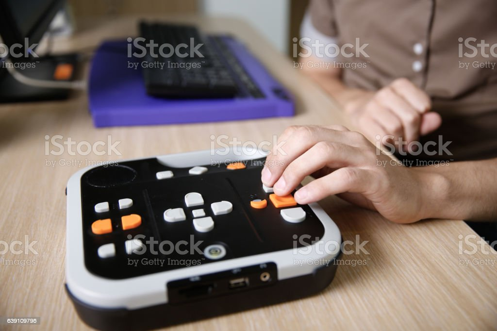 Blind person using audio book player for visually impaired stock photo