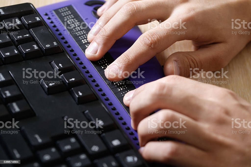 Blind person using computer with braille computer display stock photo