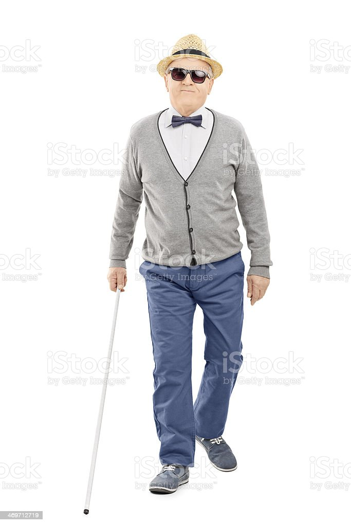 Blind senior gentleman walking with a stick stock photo