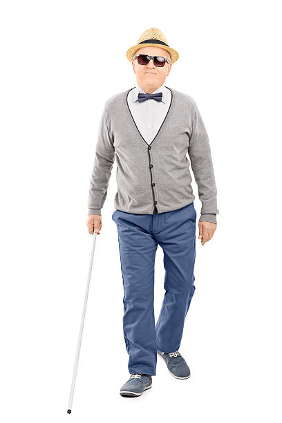 Blind senior gentleman walking with a stick stock photo