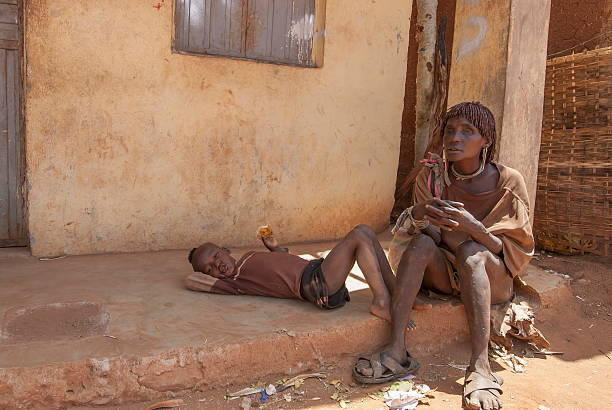 blind woman takes a rest in dimeka, valley omo, ethiopia. - horn of africa stock photos and pictures