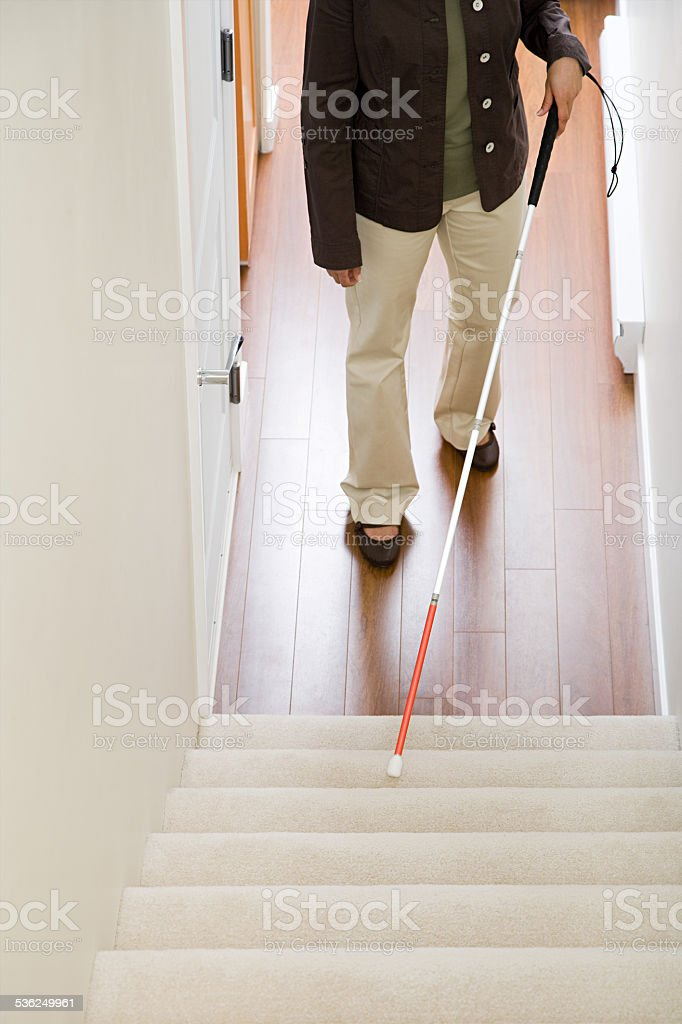 Blind woman using a walking stick on stairway stock photo