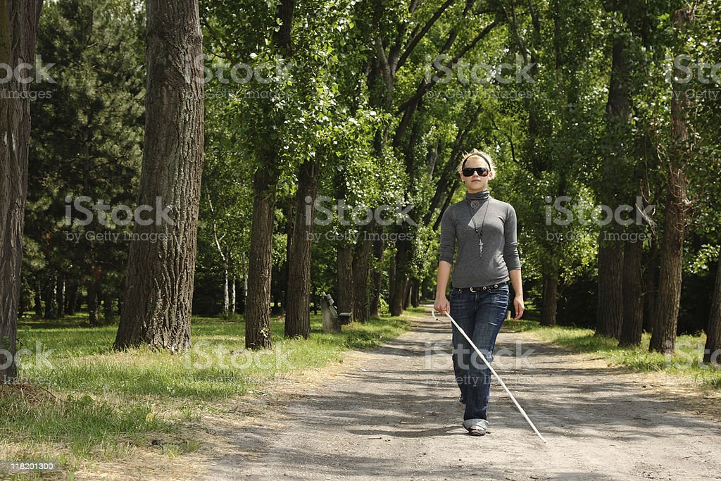 blind woman walking in a park stock photo