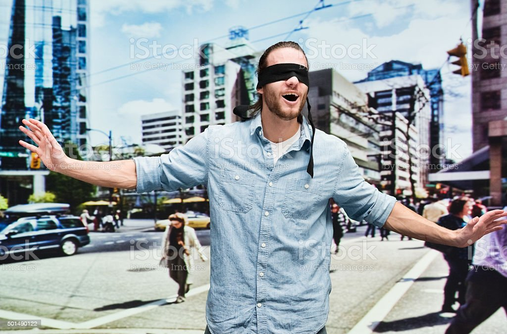 Blindfold man outdoors with arms outstretched stock photo