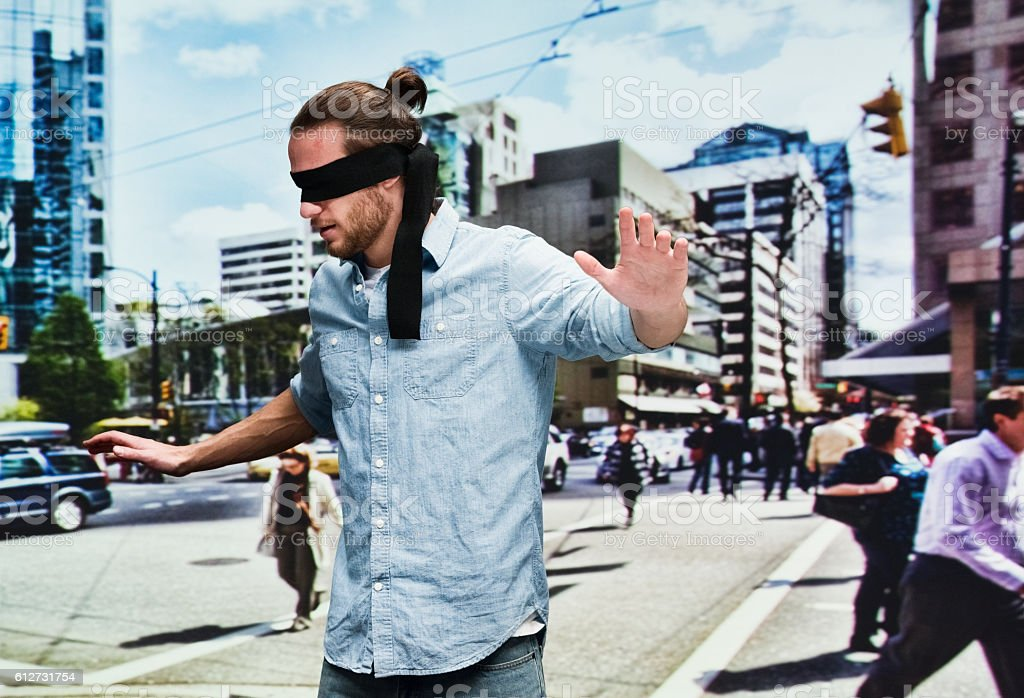 Blindfold man searching outdoors stock photo
