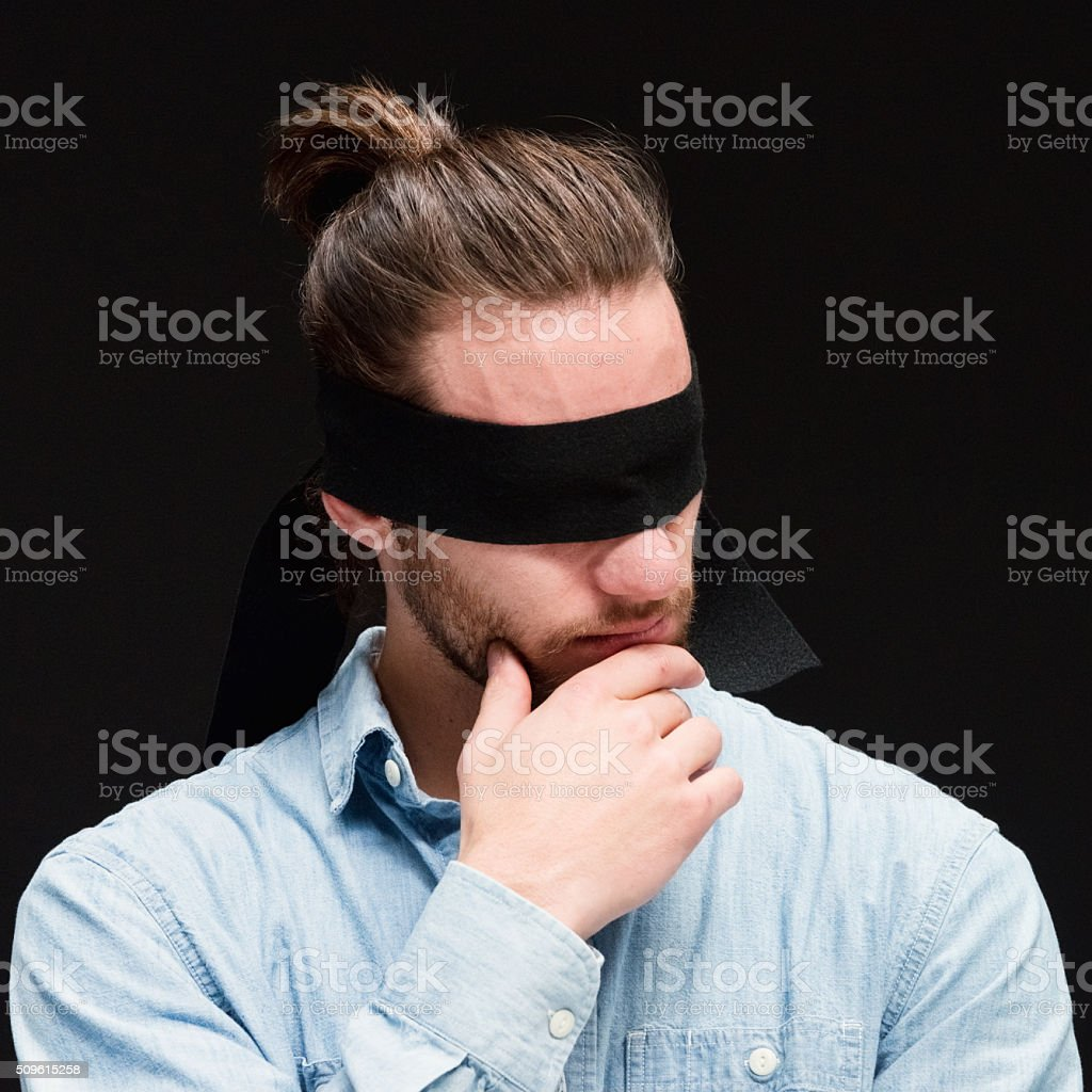 Blindfold man standing and looking away stock photo