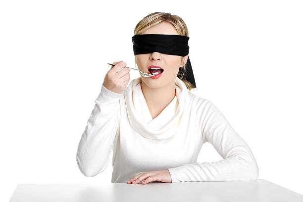 Blindfold woman eating pills stock photo