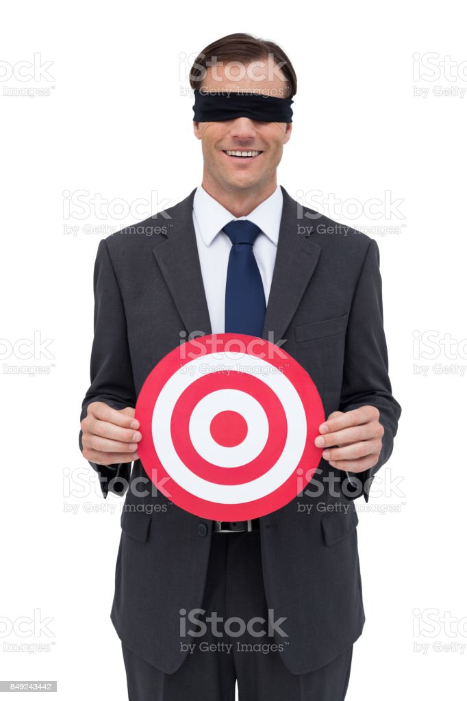 Blindfolded and smiling businessman holding a red target stock photo