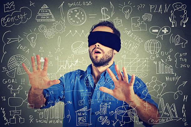 Blindfolded business man walking through social media financial data stock photo