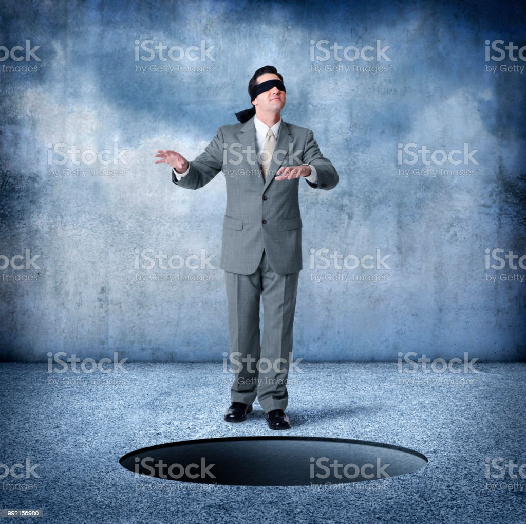 Blindfolded Businessman About To Step Into Large Hole stock photo