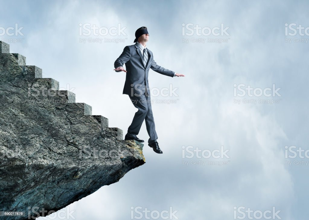 Blindfolded Businessman About To Step Off Stairs stock photo